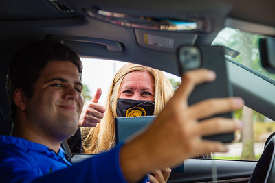 Suncoast High School student Adrian Demce takes a selfie with Principal Kathryn Koerner after getting his diploma at Suncoast High School in Riviera Beach, Wednesday, May 27, 2020. Suncoast High School gave out caps and gowns and other items along with the prized diplomas in a drive through fashion at the school. [JOSEPH FORZANO/palmbeachpost.com]