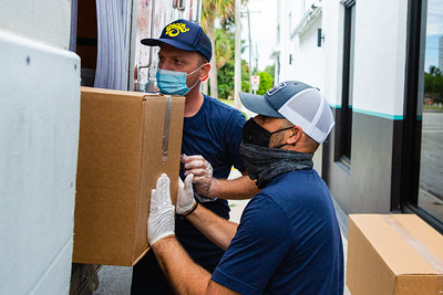 Mario Belan , left and Adam Yazinka load a box of meals into a refrigerated truck outside of Grato in West Palm Beach on Wednesday, June 17, 2020. The hospitality group that owns Grato and Buccan has started a charity effort called Buccan Provisions to help feed the under-served in the community. Chef Zach Bell has turned the dining room at Grato into a meal prep and packaging assembly line that's putting out 15,000 meals a week for area needy. [JOSEPH FORZANO/palmbeachpost.com]