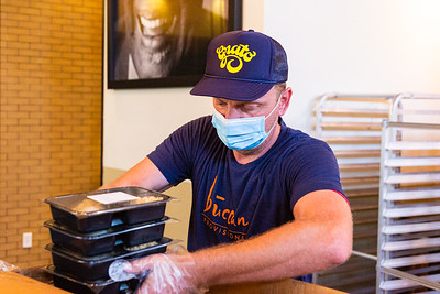Mario Belan stacks packaged meals in a box at Grato in West Palm Beach on Wednesday, June 17, 2020. The hospitality group that owns Grato and Buccan has started a charity effort called Buccan Provisions to help feed the under-served in the community. Chef Zach Bell has turned the dining room at Grato into a meal prep and packaging assembly line that's putting out 15,000 meals a week for area needy. [JOSEPH FORZANO/palmbeachpost.com]