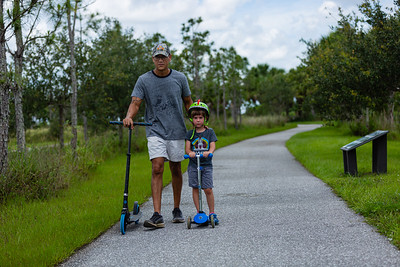 David Cicero, left, and son Sethino, age 4, of Wellington, ride scooters on one of the trails at the Wellington Environmental Preserve in Wellington, Monday, June 22, 2020. [JOSEPH FORZANO/palmbeachpost.com]