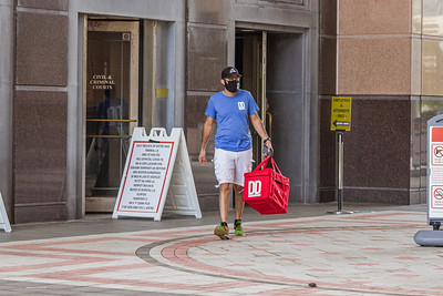A mask wearing Delivery Dudes employee leaves the Palm Beach County Courthouse in West Palm Beach, Wednesday, June 24, 2020. Palm Beach County commissioners unanimously agreed that masks must be worn in all buildings where the public is welcome to help fight the spread of coronavirus. [JOSEPH FORZANO/palmbeachpost.com]