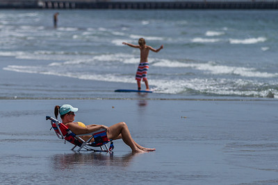 A woman relaxes in the surf while a boy skim boards in the background at Ocean Hammock Ridge Park in Boynton Beach, Tuesday, June 30, 2020. Due to the rise in coronavirus cases, Palm Beach County will close beaches Friday, July 3 to help fight the spread of the disease. [JOSEPH FORZANO/palmbeachpost.com]