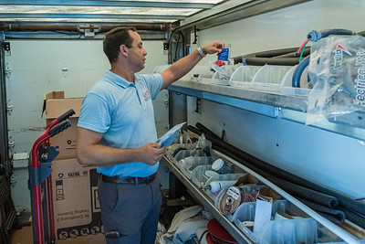 Rey Riviera, co-owner of TCS (Temperature Control Solutions) in West Palm Beach, looks for parts in his work van in Lake Worth on Wednesday, July 1, 2020. [JOSEPH FORZANO/palmbeachpost.com]