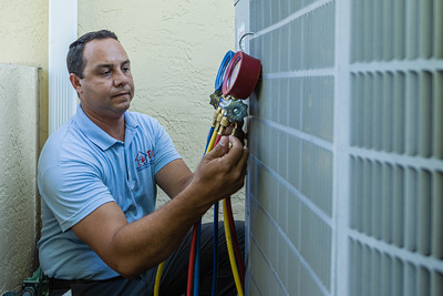 Rey Riviera, co-owner of TCS (Temperature Control Solutions) in West Palm Beach, works on an air conditioner compressor in Lake Worth on Wednesday, July 1, 2020. [JOSEPH FORZANO/palmbeachpost.com]