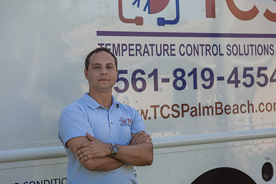 Rey Riviera, co-owner of TCS (Temperature Control Solutions) poses for a photo in front of his work van in Lake Worth on Wednesday, July 1, 2020. [JOSEPH FORZANO/palmbeachpost.com]