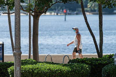A man wearing a protective mask walks along the waterfront in downtown West Palm Beach on Wednesday, July 15, 2020.  [JOSEPH FORZANO/palmbeachpost.com]