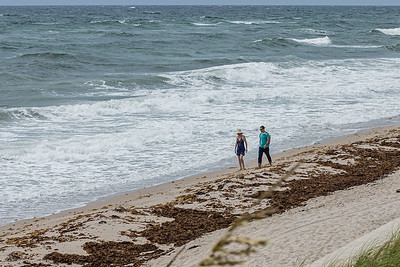 A couple walks along the shore at Lantana Municipal Beach, Tuesday, July 21, 2020. A 12 knot easterly wind created some large waves and piled sargassum on the shore. [JOSEPH FORZANO/palmbeachpost.com]