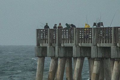 Fisherman in rain gear brave the rain and thunder to fish from the William O. Lockhart Municipal Pier in Lake Worth Beach, Thursday, July 23, 2020. [JOSEPH FORZANO/palmbeachpost.com]