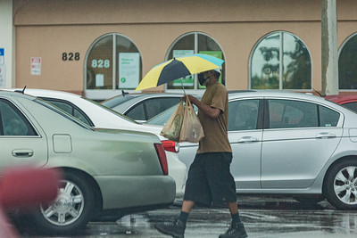 A man walks to his car under his umbrella with his groceries from the Publix at the Southdale Shopping Center in West Palm Beach, Thursday, July 23, 2020. [JOSEPH FORZANO/palmbeachpost.com]