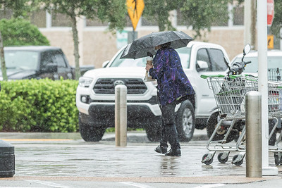 A woman shelters under her umbrella during a heavy shower as she walks across the Publix parking lot in Lake Worth Beach, Thursday, July 23, 2020. [JOSEPH FORZANO/palmbeachpost.com]