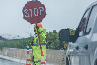 A worker in rain gear on A1A in Palm Beach stops traffic as construction has A1A down to one lane, Thursday, July 23, 2020. [JOSEPH FORZANO/palmbeachpost.com]