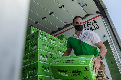 Steve McKracken, the Sergeant at Arms of the West Palm Beach Chapter of the American Culinary Federation and Head Chef at Edgwater at Boca Pointe, unload boxes of produce from the back of the trailer where it is being distributed in the parking lot of the Home Depot on Northlake Blvd. in Lake Park, Friday, July 24, 2020. In conjunction with Home Depot, the ACF has been distributing food for free at this location for the past three Fridays and will back for the next three Fridays. Over 1,440 boxes of produce will be distributed today. The boxes contain various items of fresh produce including lettuce, plums and other fruits and vegetables. [JOSEPH FORZANO/palmbeachpost.com]