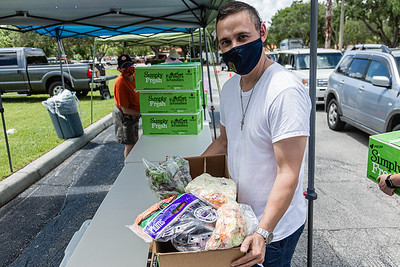 Joseph Water, the First Vice President of the West Palm Beach Chapter of the American Culinary Federation, holds one of the boxes of produce being distributed for free in the parking lot of the Home Depot on Northlake Blvd. in Lake Park, Friday, July 24, 2020. In conjunction with Home Depot, the ACF has been distributing food at this location for the past three Fridays and will back for the next three Fridays. Over 1,440 boxes of produce will be distributed today. The boxes contain various items of fresh produce including lettuce, plums and other fruits and vegetables. [JOSEPH FORZANO/palmbeachpost.com]