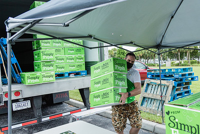 Steve McKracken, the Sergeant at Arms of the West Palm Beach Chapter of the American Culinary Federation and Head Chef at Edgwater at Boca Pointe, carries boxes of produce from the back of the trailer to the tables where it is being distributed in the parking lot of the Home Depot on Northlake Blvd. in Lake Park, Friday, July 24, 2020. In conjunction with Home Depot, the ACF has been distributing food for free at this location for the past three Fridays and will back for the next three Fridays. Over 1,440 boxes of produce will be distributed today. The boxes contain various items of fresh produce including lettuce, plums and other fruits and vegetables. [JOSEPH FORZANO/palmbeachpost.com]