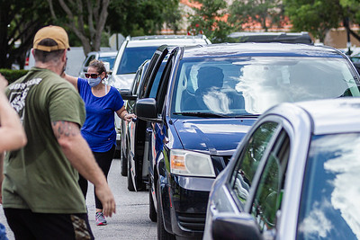 A line of cars stretches through the Home Depot parking lot on Northlake Blvd. and I95 in Lake Park as people queue up for free boxes of produce, Friday, July 24, 2020. In conjunction with Home Depot, the West Palm Beach Chapter of the American Culinary Federation has been distributing food at this location for the past three Fridays and will back for the next three Fridays. Over 1,440 boxes of produce will be distributed today. The boxes contain various items of fresh produce including lettuce, plums and other fruits and vegetables. [JOSEPH FORZANO/palmbeachpost.com]