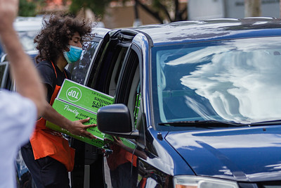 Home Depot employee Elijah Moreno places a two boxes of produce in a car in the parking lot of the Home Depot on Northlake Blvd. in Lake Park, Friday, July 24, 2020. In conjunction with Home Depot, the ACF has been distributing food for free at this location for the past three Fridays and will back for the next three Fridays. Over 1,440 boxes of produce will be distributed today. The boxes contain various items of fresh produce including lettuce, plums and other fruits and vegetables. [JOSEPH FORZANO/palmbeachpost.com]