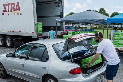 Joseph Water, the First Vice President of the West Palm Beach Chapter of the American Culinary Federation, places two boxes of produce in a car in the parking lot of the Home Depot on Northlake Blvd. in Lake Park, Friday, July 24, 2020. In conjunction with Home Depot, the ACF has been distributing food for free at this location for the past three Fridays and will back for the next three Fridays. Over 1,440 boxes of produce will be distributed today. The boxes contain various items of fresh produce including lettuce, plums and other fruits and vegetables. [JOSEPH FORZANO/palmbeachpost.com]