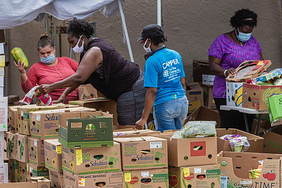 Volunteers sort food items for a food giveaway at Above the Sea Restaurant on Wingfield Street in Lake Worth Beach, Tuesday, July 28, 2020. The restaurant, owned by Patrick Livingston, has been providing food and hot meals to community members since 2011. [JOSEPH FORZANO/palmbeachpost.com]