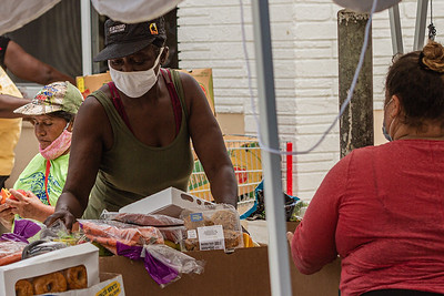 Members of the community receive various food items during a food drive at Above the Sea Restaurant on Wingfield Street in Lake Worth Beach, Tuesday, July 28, 2020. The restaurant, owned by Patrick Livingston, has been providing food and hot meals to community members since 2011. [JOSEPH FORZANO/palmbeachpost.com]