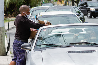 A volunteer places a box of food items in a car at the Above the Sea Restaurant on Wingfield Street in Lake Worth Beach, Tuesday, July 28, 2020. The restaurant, owned by Patrick Livingston, has been providing food and hot meals to community members since 2011. [JOSEPH FORZANO/palmbeachpost.com]