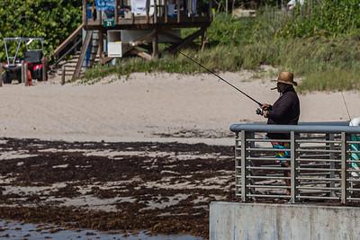 A man smokes a cigar while fishing off the jetty at the Boynton Inlet in Boynton Beach, July 31, 2020. [JOSEPH FORZANO/palmbeachpost.com]