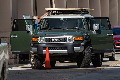 A man secures a load of plywood to the roof rack of his Toyota FJ Cruiser at the Home Depot on Palm Beach Lakes Blvd. in West Palm Beach, Friday, July 31, 2020, in preparation for Hurricane Isaias. [JOSEPH FORZANO/palmbeachpost.com]