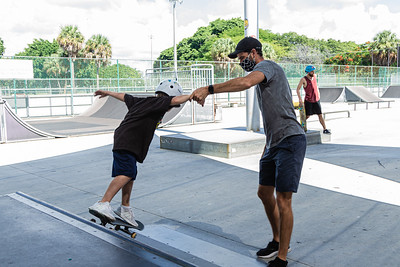 Skate instructor Derek McLean or West Palm Beach and Manager at Phipps Park Skatepark helps Beau Baxter or West Palm Beach perform a trick on a ramp at Phipps Park Skatepark, Monday, August 10, 2020. [JOSEPH FORZANO/palmbeachpost.com]