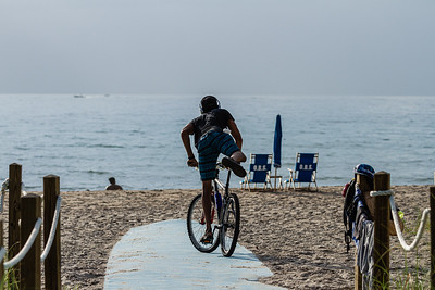 A man dismounts from his bicycle at the Delray Public Beach on South Ocean Blvd., Thursday, August 20, 2020. [JOSEPH FORZANO/palmbeachpost.com]