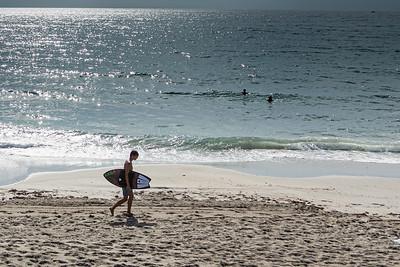 A skim boarder walks along the beach at South Beach Park in Boca Raton near Palmetto Park Road, Thursday, August 20, 2020. [JOSEPH FORZANO/palmbeachpost.com]