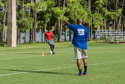 Rodendy Joachim, 11, of Royal Palm Beach runs a drill under the watchful eye of his father Ronald, who was a soccer coach before COVID-19 at Okeeheelee Park, Tuesday, August 25, 2020. [JOSEPH FORZANO/palmbeachpost.com]
