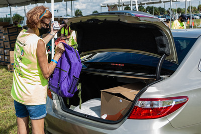 A Back to School PBC! volunteer places a backpack full of school supplies in the trunk of a car at the Back to School PBC! event held at the lot across from the Palm Beach Kennel Club in West Palm Beach, Saturday, August 29, 2020. Back to School PBC! has partnered with several agencies and has 6 sites throughout Palm Beach County which will supply roughly 10,000 students with school supplies and food. [JOSEPH FORZANO/palmbeachpost.com]