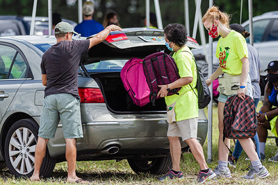 Back to School PBC! volunteers place a backpacks full of school supplies in the trunk of a car at the Back to School PBC! event held at the lot across from the Palm Beach Kennel Club in West Palm Beach, Saturday, August 29, 2020. Back to School PBC! has partnered with several agencies and has 6 sites throughout Palm Beach County which will supply roughly 10,000 students with school supplies and food. [JOSEPH FORZANO/palmbeachpost.com]