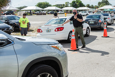 A Palm Beach County Sheriff's Deputy directs traffic at the lot across the street from the Palm Beach Kennel Club in West Palm Beach, where Back to School PBC! and other agencies were holding a by invitation only school supply giveaway, Saturday, August 29, 2020. Over 4,500 people were expected at the event at the Kennel Club. Back to School PBC! Has partnered with several agencies and has 6 sites throughout Palm Beach County which will supply roughly 10,000 students with school supplies and food. [JOSEPH FORZANO/palmbeachpost.com]