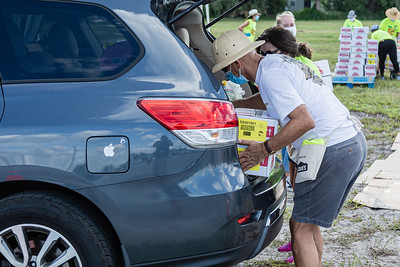 A Back to School PBC! volunteer places a two boxes of non perishable food  in the trunk of a car at the Back to School PBC! event held at the lot across from the Palm Beach Kennel Club in West Palm Beach, Saturday, August 29, 2020. Back to School PBC! has partnered with several agencies and has 6 sites throughout Palm Beach County which will supply roughly 10,000 students with school supplies and food. [JOSEPH FORZANO/palmbeachpost.com]