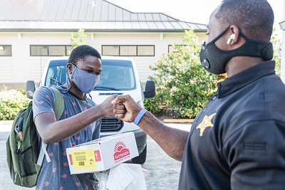Clark Merilien, 17, who attends William T. Dwyer High School, fist bumps Palm Beach County Sheriff's Deputy Anthony Dukes after receiving a backpack of school supplies and a box of non-perishable food at the Colony Youth Center on Alternate A1A in Palm Beach Gardens, Saturday, August 29, 2020. Back to School PBC! Has partnered with several agencies and has 6 sites throughout Palm Beach County which will supply roughly 10,000 students with school supplies and food. [JOSEPH FORZANO/palmbeachpost.com]