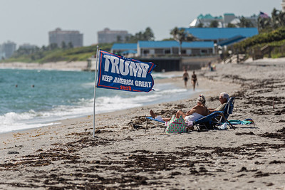 A couple relaxes on the beach in Jupiter next to their Trump 2020 flag, Wednesday, September 02, 2020. [JOSEPH FORZANO/palmbeachpost.com]