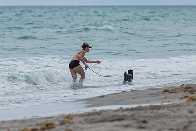 A woman plays with her dog in the surf at Juno Beach, Friday, September 11, 2020. [JOSEPH FORZANO/palmbeachpost.com]