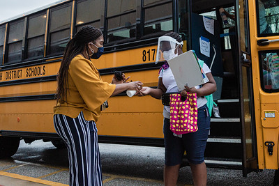 Assistant Principal Dr. Andrea Walker, greets students and sprays hand sanitizer into their hands as they get off the bus at Lincoln Elementary School in Riviera Beach, Monday, September 21, 2020. Today was the first day of in person schooling since the outbreak of the COVID-19 pandemic. [JOSEPH FORZANO/palmbeachpost.com]