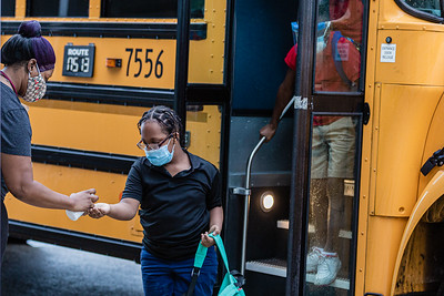 Teacher's aid Andresa Holzandorf, greets students and sprays hand sanitizer into their hands as they get off the bus at Lincoln Elementary School in Riviera Beach, Monday, September 21, 2020. Today was the first day of in person schooling since the outbreak of the COVID-19 pandemic. [JOSEPH FORZANO/palmbeachpost.com]