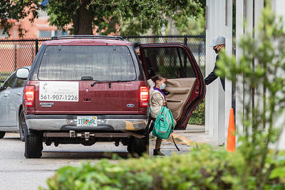 A girl gets out of her car and is greeted by a staff member at Lincoln Elementary School in Riviera Beach, Monday, September 21, 2020. Today was the first day of in person schooling since the outbreak of the COVID-19 pandemic. [JOSEPH FORZANO/palmbeachpost.com]
