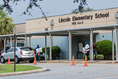 Staff members at Lincoln Elementary School in Riviera Beach, await students at the parent drop off with welcoming signs, Monday, September 21, 2020. Today was the first day of in person schooling since the outbreak of the COVID-19 pandemic. [JOSEPH FORZANO/palmbeachpost.com]