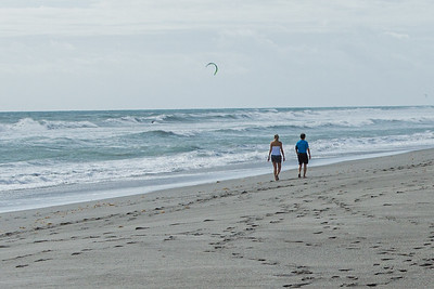 A couple walks along Juno Beach as a kite surfer glides over the rough seas caused by strong easterly winds off of Juno Beach, Thursday, September 24, 2020. [JOSEPH FORZANO/palmbeachpost.com]