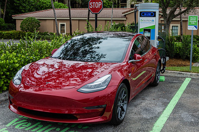 Using a Tesla charging adapter, a Tesla sedan gets a charge at the new EVolution charging station at Midtown in Palm Beach Gardens, Friday, October 2, 2020. There are four Level 3 (fast) charging stations, and two Level 2 (slower charging) stations at the site. Florida Power & Light is commemorating National Drive Electric Week with the debut of a new electric vehicle universal fast-charging station at Mainstream in Midtown in Palm Beach Gardens. Customers will be charged about 30 cents per kilowatt hour to charge their electric vehicles. [JOSEPH FORZANO/palmbeachpost.com]