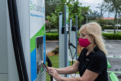 Beth Bowers, Project Manager of FPL EVolution uses her smartphone to connect to the Level 3 charging station at the new EVolution charging station at Midtown in Palm Beach Gardens, Friday, October 2, 2020. There are four Level 3 (fast) charging stations, and two Level 2 (slower charging) stations at the site. Florida Power & Light is commemorating National Drive Electric Week with the debut of a new electric vehicle universal fast-charging station at Mainstream in Midtown in Palm Beach Gardens. Customers will be charged about 30 cents per kilowatt hour to charge their electric vehicles. [JOSEPH FORZANO/palmbeachpost.com]
