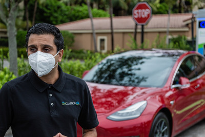Anuj Chokshi, FPL Development Project Director for E-Mobility, talks to the media while his Telsa charges in the background at the new EVolution charging station at Midtown in Palm Beach Gardens, Friday, October 2, 2020. There are four Level 3 (fast) charging stations, and two Level 2 (slower charging) stations at the site. Florida Power & Light is commemorating National Drive Electric Week with the debut of a new electric vehicle universal fast-charging station at Mainstream in Midtown in Palm Beach Gardens. Customers will be charged about 30 cents per kilowatt hour to charge their electric vehicles. [JOSEPH FORZANO/palmbeachpost.com]