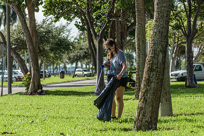 A volunteer gathers trash at the Currie Park Marina in West Palm Beach, Sunday, October 11, 2020. A group of volunteers is doing their part to clean up to try and clean up the pervasive litter problem in West Palm Beach. (JOSEPH FORZANO / THE PALM BEACH POST)