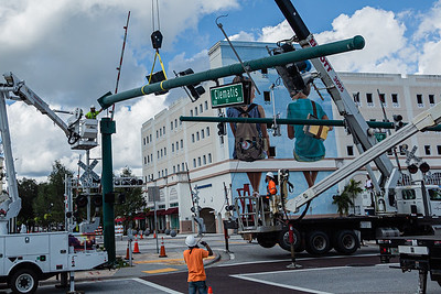 Construction crews work to remove the Clematis Street sign that hangs across Quadrille Blvd. in preparation for the passage of the Edgewater building, Sunday, October 11, 2020. The 1920′s-era rooming house at 316 Gardenia, is headed for a new life as a bed and breakfast in the city's Historic Northwest. (JOSEPH FORZANO / THE PALM BEACH POST)