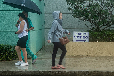 A couple walks back to their car under their umbrella having just voted early, as a woman in a rain slicker walks toward the line for early voting at the Palm Beach County Library on Summit Blvd., Monday, October 19, 2020. Statewide early voting started today. (JOSEPH FORZANO / THE PALM BEACH POST)