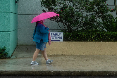 A woman walks under the protection of her umbrella toward the early voting site at the Palm Beach County Library on Summit Blvd., Monday, October 19, 2020. Statewide early voting started today. (JOSEPH FORZANO / THE PALM BEACH POST)