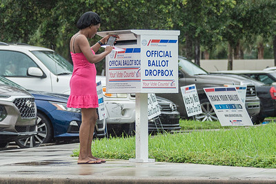 A woman drops her mail in ballot at the official ballot dropbox at the Supervisor of Elections Office in West Palm Beach during a very light rain, Wednesday, October 21, 2020. (JOSEPH FORZANO / THE PALM BEACH POST)